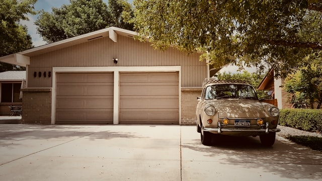 Alt-text: Car parked in front of a garage