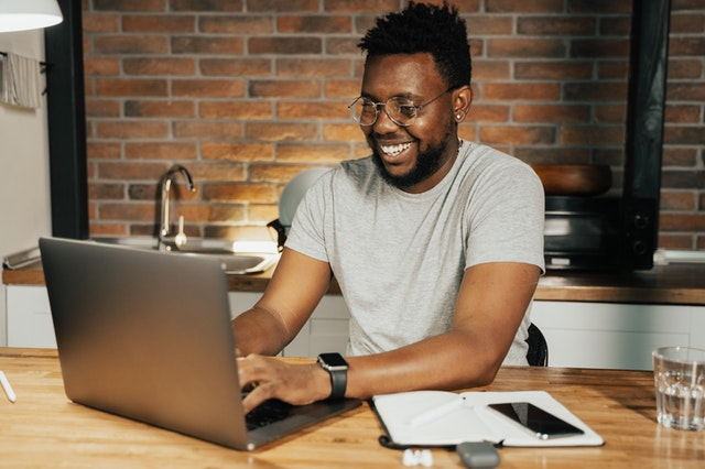 MAN SMILING AND WORKING ON HIS COMPUTER