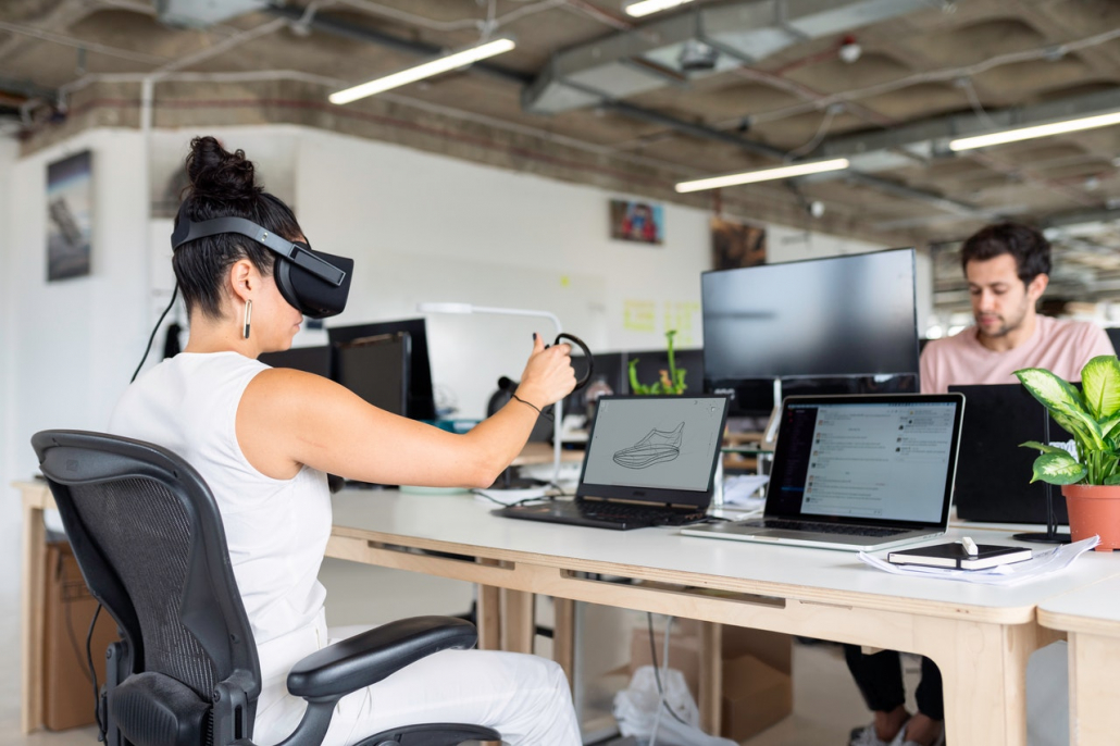 A person with a VR headset in front of a laptop.