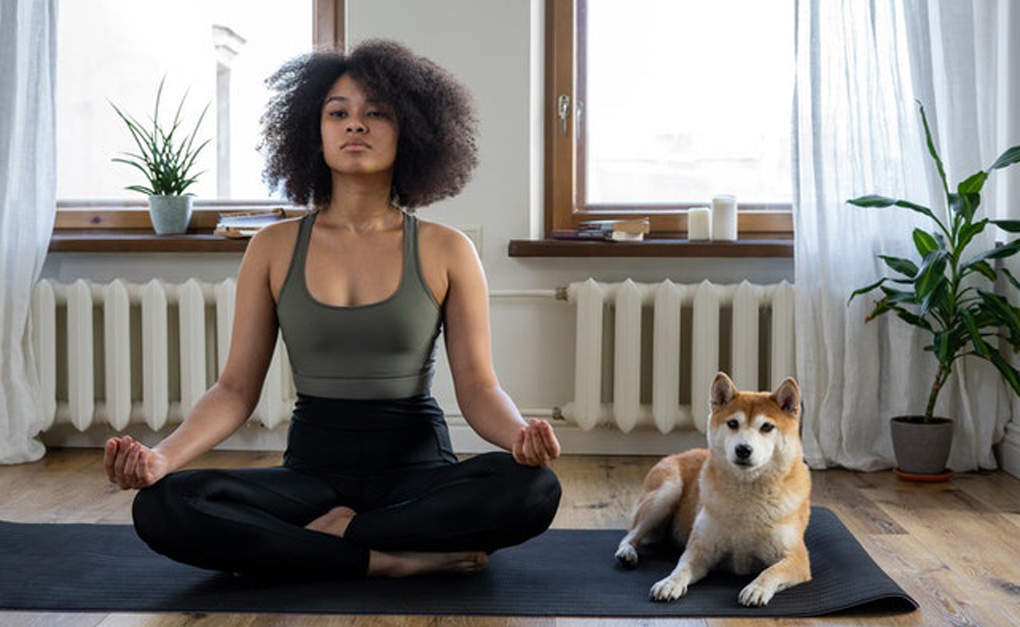 Alt-tag: A woman and her dog sitting on a yoga mat.
