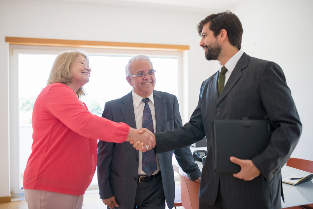 A real estate agent shaking hands with clients after buying a home in New Zealand.